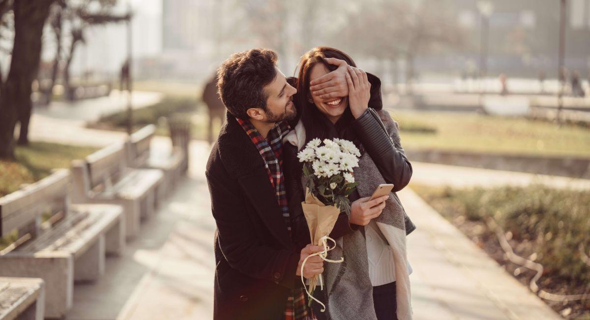 Mann überrascht Frau mit Blumen zum Valentinstag